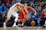 Phoenix Suns guard Devin Booker (1) and New Orleans Pelicans guard Kenrich Williams reach for the ball during the first half of an NBA basketball game in New Orleans, Thursday, Dec. 5, 2019. (AP Photo/Gerald Herbert)