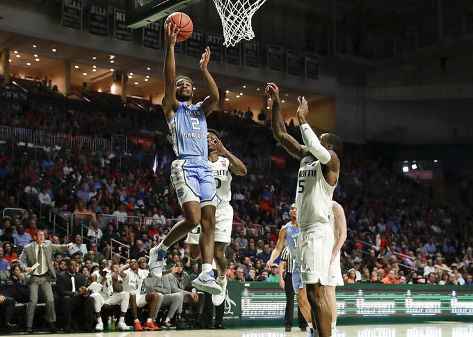 North Carolina Tar Heels guard Coby White shoots and scores against Miami Hurricanes guard Chris Lykes during the first half of an NCAA college basketball game on Saturday, Jan. 19, 2019, in Coral Gables, Fla. (AP Photo/Brynn Anderson)