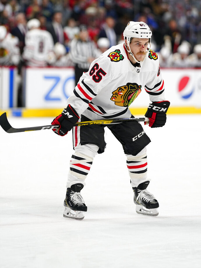 Chicago Blackhawks center Andrew Shaw, with a cut on his nose, looks on before a face off against the Colorado Avalanche during the second period of an NHL hockey game Saturday, Nov. 30, 2019, in Denver. (AP Photo/Jack Dempsey)
