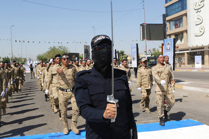 FILE - In this May 31, 2019, file photo, Iraqi Popular Mobilization Forces march in Baghdad, Iraq. Iraq's government is moving to limit the influence of powerfully Iran-backed militias in the country, placing them under the full command of the Iraqi armed forces. In a decree issued Monday night, Prime Minister Adel Abdul-Mahdi says militias says militia offices who continue to operate independently will be closed and any armed faction working