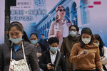 People wearing protective face masks walk on a street in the Central, the business district of Hong Kong, Tuesday, Feb. 11, 2020. China's daily death toll from new virus has topped 100 for first time, with more than 1,000 total deaths recorded, the health ministry announced Tuesday, as the spread of the contagion shows little sign of abating while exacting an ever-rising cost. (AP Photo/Kin Cheung)