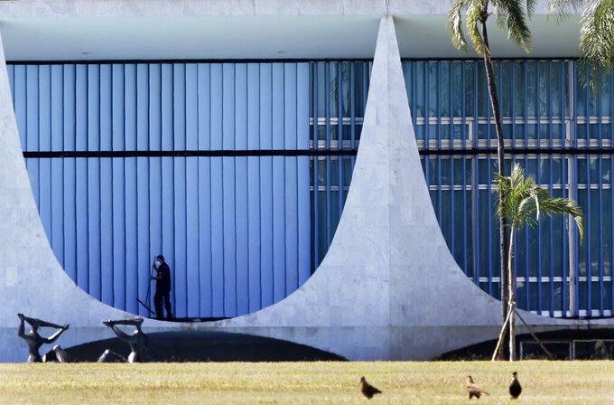 A worker cleans outside the presidential residence, Alvorada Palace, in Brasilia, Brazil, Tuesday, July 7, 2020. Bolsonaro said Tuesday he has tested positive for COVID-19. (AP Photo/Eraldo Peres)