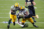 New Orleans Saints running back Alvin Kamara (41) is tackled by Green Bay Packers strong safety Adrian Amos (31) and inside linebacker Christian Kirksey (58) on a 49 yard run in the first half of an NFL football game in New Orleans, Sunday, Sept. 27, 2020. (AP Photo/Brett Duke)