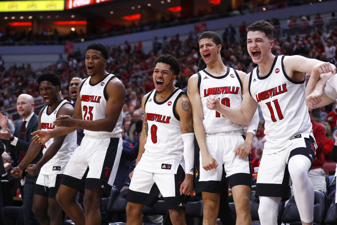 Louisville bench reacts to a dunk during the second half of an NCAA college basketball game against Syracuse Wednesday, Feb. 19, 2020, in Louisville, Ky. Louisville won 90-66. (AP Photo/Wade Payne)