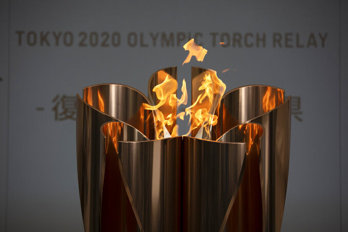 FILE - In this March 24, 2020, file photo, the Olympic Flame burns during a ceremony in Fukushima, Japan. The torch relay is kicking off from northeastern Japan. It will last 121 days and involve 10,000 runners carrying the torch to 47 Japanese prefectures. (AP Photo/Jae C. Hong, File)
