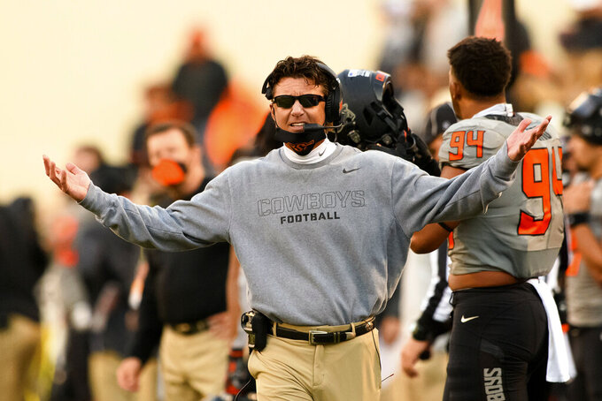 FILE - In this Saturday, Oct. 24, 2020, file photo, Oklahoma State head coach Mike Gundy gestures to an official during an NCAA college football game in Stillwater, Okla. The Sooners are are the only Big 12 team without at least two losses, even though none has played more than six games.  (AP Photo/Brody Schmidt, File)