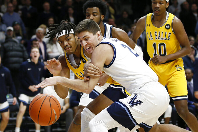 La Salle's Ed Croswell, left, and Villanova's Collin Gillespie struggle for the ball during the first half of an NCAA college basketball game, Sunday, Dec. 1, 2019, in Villanova, Pa. (AP Photo/Matt Slocum)
