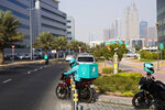 A delivery driver for the app Deliveroo prepares to make a delivery, in Dubai, United Arab Emirates, Thursday, Sept. 9, 2021. Advocates and workers say that casualties among food delivery riders are mounting in the city of Dubai, as the pandemic accelerates a boom in customer demand. (AP Photo/Jon Gambrell)