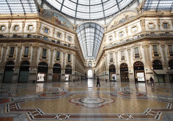 A city police officer walks in the Vittorio Emanuele II gallery shopping arcade in downtown Milan, Italy, Friday, Nov. 6, 2020. Lombardy is among the four Italian regions classified as red zones, where a strict lockdown was imposed starting Friday - to be reassessed in two weeks - in an effort to curb the COVID-19 infections growing curve. Starting today, only shops selling food and other essentials are allowed to open. (AP Photo/Antonio Calanni)