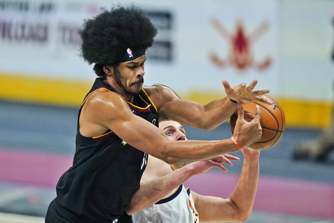 Cleveland Cavaliers' Jarrett Allen, left and Denver Nuggets' Nikola Jokic reach for the ball during the first half of an NBA basketball game, Friday, Feb. 19, 2021, in Cleveland. (AP Photo/Tony Dejak)