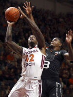 Virginia Tech's Ty Outlaw (42) shoots past Miami's Anthony Lawrence II (3) during the first half of NCAA college basketball game in Blacksburg, Va., Friday, March 8, 2019. (Matt Gentry/The Roanoke Times via AP)