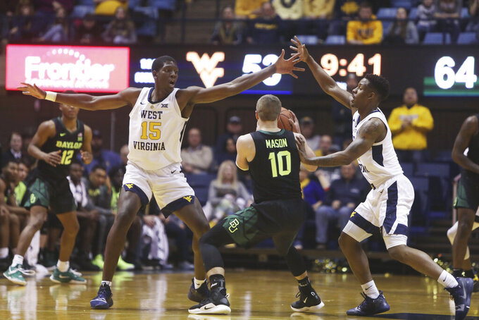 West Virginia forward Lamont West (15) and guard Brandon Knapper (2) trap Baylor guard Makai Mason (10) during the second half of an NCAA college basketball game Monday, Jan. 21, 2019, in Morgantown, W.Va. (AP Photo/Raymond Thompson)