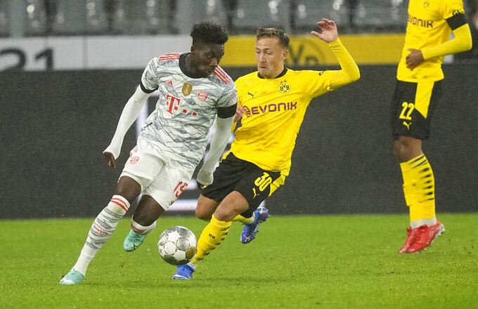 Bayern's Chris Richards, left, challenges for the ball with Dortmund's Felix Passlack during the German Supercup soccer match between Borussia Dortmund and Bayern Munich in Dortmund, Germany, Tuesday, Aug. 17, 2021. (AP Photo/Martin Meissner)