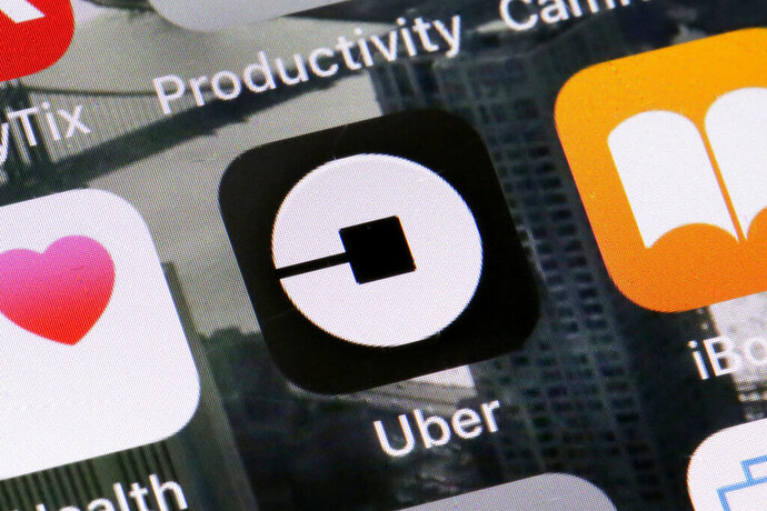 FILE - This Tuesday, June 12, 2018, file photo shows the Uber app on a phone in New York. Uber on Thursday, April 18, 2019, said that it is releasing a new feature to help riders ensure they're getting into the right vehicles. The development comes several weeks after a University of South Carolina student was killed after getting into a car she had mistaken for the Uber ride she hailed. (AP Photo/Richard Drew, File)