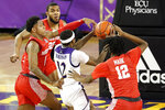 East Carolina's Tremont Robinson-White (12) drives the ball between Houston's Marcus Sasser (0), Houston's Tramon Mark (12), and Houston's Reggie Chaney (32) during the first half of an NCAA college basketball game in Greenville, N.C., Wednesday, Feb. 3, 2021. (AP Photo/Karl B DeBlaker)