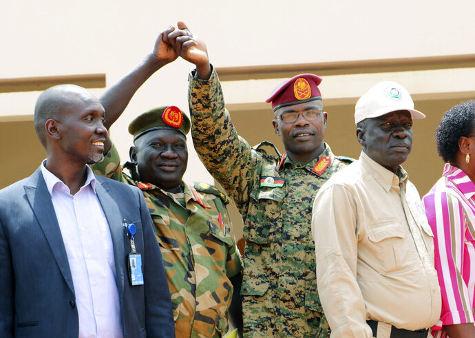 In this photo of Thursday, Jan. 1 2019, Opposition commander James Nando, third left, and the government's army commander, second left, as Government and opposition forces come together for one of many meetings aimed at building confidence for a peace deal between the opposing forces, in the town of Yambio, South Sudan, although the meeting deteriorated with both sides accused of recruiting forces and using child soldiers. Officials said Thursday Feb. 21 2019, that evidence from numerous accounts, suggest that South Sudan's rival armed groups are forcefully recruiting civilians, including child soldiers, violating a fragile peace deal signed five months ago. (AP Photo/Sam Mednick)