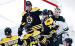 Boston Bruins left wing Jake DeBrusk (74) smiles as he is congratulated by teammates after deflecting a shot by Patrice Bergeron off his chest for a goal, beating Minnesota Wild goaltender Alex Stalock, right, during the first period of an NHL hockey game in Boston, Tuesday, Jan. 8, 2019. DeBrusk was credited with the goal. (AP Photo/Charles Krupa)