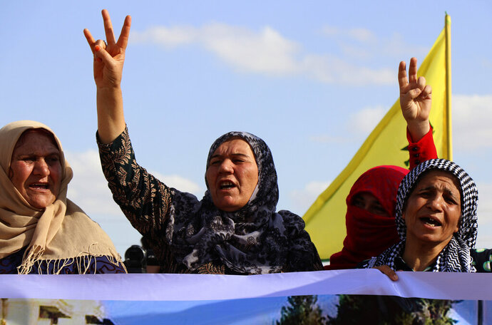 Kurdish women flash victory signs and shout slogans as they protest against possible Turkish military operation on their areas, at the Syrian-Turkish border, in Ras al-Ayn, Syria, Monday, Oct. 7, 2019. Syria's Kurds accused the U.S. of turning its back on its allies and risking gains made in the fight against the Islamic State group as American troops began pulling back on Monday from positions in northeastern Syria ahead of an expected Turkish assault. (AP Photo)