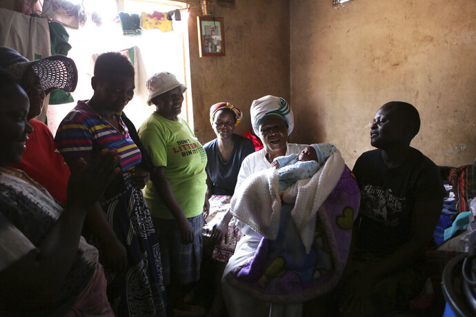 72-year old grandmother Esther Zinyoro Gwena holds one of the babies she helped deliver in her tiny apartment in the poor surburb of Mbare in Harare, Zimbabwe, in this Saturday, Nov. 16, 2019.  Grandmother Esther Zinyoro Gwena claims to be guided by the holy spirit and has become a local hero, as the country's economic crisis forces closure of medical facilities, and mothers-to-be seek out untrained birth attendants.(AP Photo/Tsvangirayi Mukwazhi)