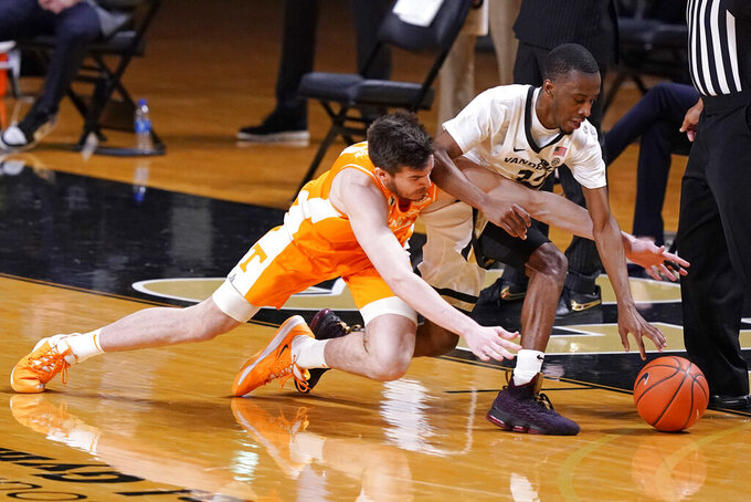 Tennessee's John Fulkerson, left, knocks the ball away from Vanderbilt's Trey Thomas, right, in the second half of an NCAA college basketball game Wednesday, Feb. 24, 2021, in Nashville, Tenn. (AP Photo/Mark Humphrey)