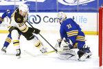 Buffalo Sabres goalie Dustin Tokarski (31) stops Boston Bruins forward Curtis Larzar (20) during the first period of an NHL hockey game, Thursday, April 22, 2021, in Buffalo, N.Y. (AP Photo/Jeffrey T. Barnes)