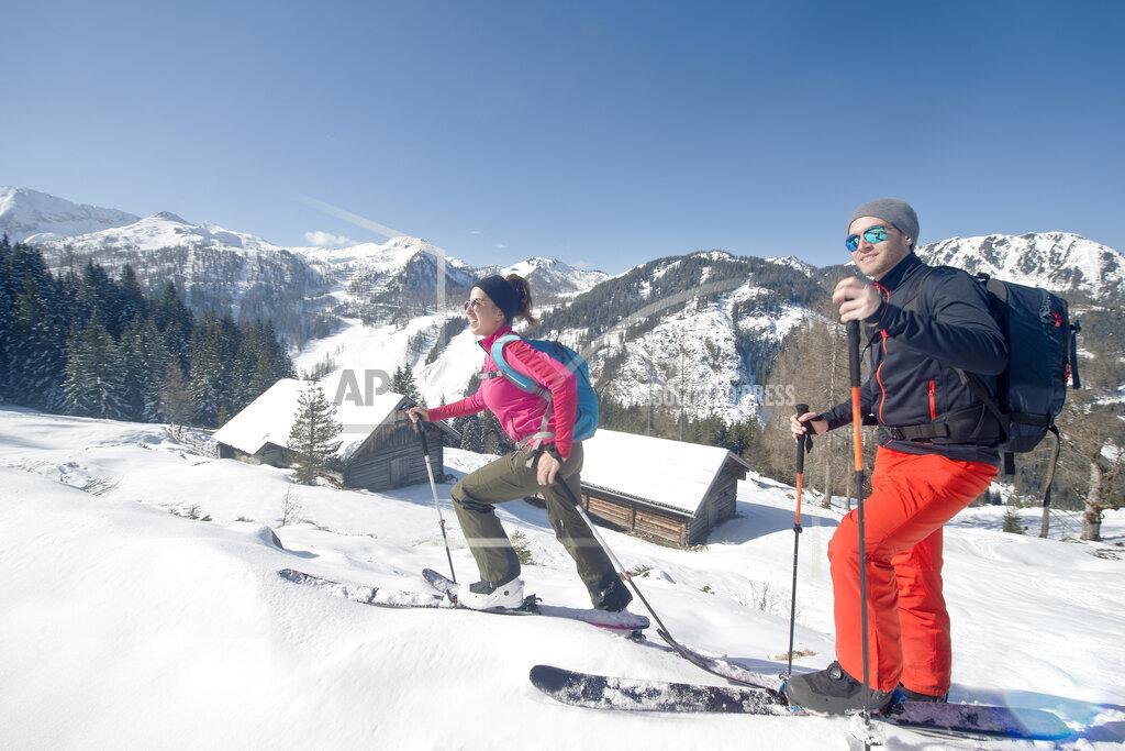 Smiling young couple enjoying ski touring during vacation