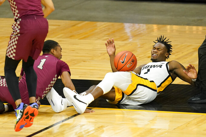 Iowa guard Joe Toussaint, right, loses the ball out of bounds in front of North Carolina Central guard Mike Melvin, left, during the first half of an NCAA college basketball game, Wednesday, Nov. 25, 2020, in Iowa City, Iowa. (AP Photo/Charlie Neibergall)