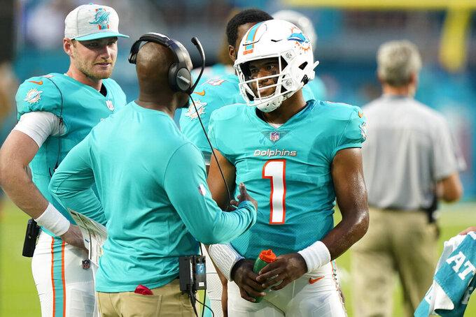 Miami Dolphins quarterback Tua Tagovailoa (1) talks to head coach Brian Flores during the first half of a NFL preseason football game against the Atlanta Falcons, Saturday, Aug. 21, 2021, in Miami Gardens, Fla. (AP Photo/Wilfredo Lee)
