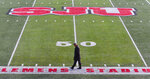 Former St. John's University football player Chuck Williams, a 1982 graduate, walks across the football field alone before the funeral of coach John Gagliardi, Monday, Oct. 15, 2018, at the St. John's Abbey in Collegeville, Minn. Using unconventional methods at the small private university in Minnesota, Gagliardi won more football games than anybody who has ever coached in college. Gagliardi died Sunday, Oct. 7, 2018, at the age of 91. (Jason Wachter/St. Cloud Times via AP)