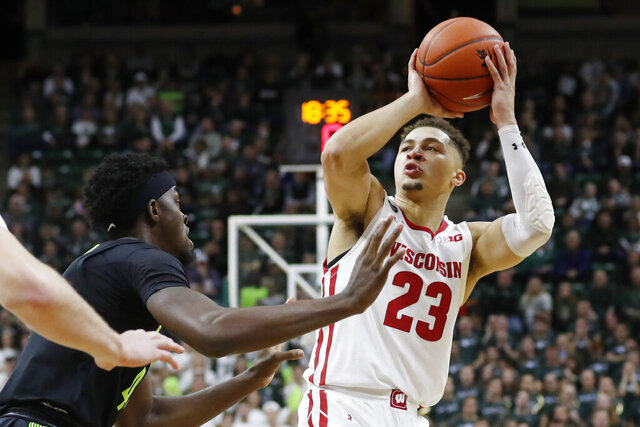 Wisconsin guard Kobe King (23) shoots over the defense of Michigan State forward Gabe Brown during the first half of an NCAA college basketball game, Friday, Jan. 17, 2020, in East Lansing, Mich. (AP Photo/Carlos Osorio)