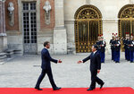 Japan's Crown Prince Naruhito, right, is greeted by French President Emmanuel Macron before a meeting at the Chateau de Versailles, west of Paris, Wednesday, Sept. 12, 2018. Japan's Crown Prince Naruhito is for a nine-day goodwill visit in France. (AP Photo/Christophe Ena)