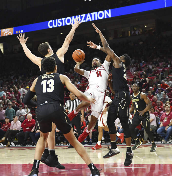 Arkansas guard Keyshawn Embery-Simpson (11) tries to get past Vanderbilt defenders Matthew Moyer (13), Yanni Wetzell, (1) and Aaron Nesmith (24) during the first half of an NCAA college basketball game, Tuesday, Feb. 5, 2019 in Fayetteville, Ark. (AP Photo/Michael Woods)