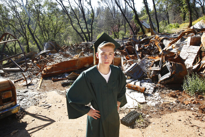 Sean Newsom, a senior at Paradise High School, poses in his cap and gown at the burnout ruins of his home in Paradise, Calif., Wednesday, June 5, 2019. After the Camp Fire destroyed the home, his parents relocated to the San Francisco Bay Area, and Newsom moved to an apartment with his older brother in Chico to finish his senior year. Newsom and the rest of the Paradise High School Class of 2019 are graduating Thursday. (AP Photo/Rich Pedroncelli)