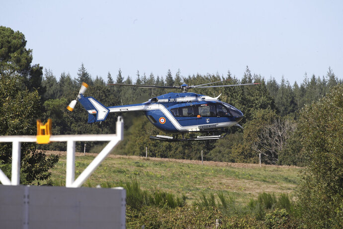 A gendarme helicopter takes off near the site of a jet crash near Pluvigner, western France, Thursday, Sept.19, 2019. A Belgian F-16 fighter jet crashed in western France, damaging a house, setting a field ablaze and leaving a pilot suspended for two hours from a high-voltage electricity line after his parachute got caught, according to French authorities. (AP Photo/David Vincent)