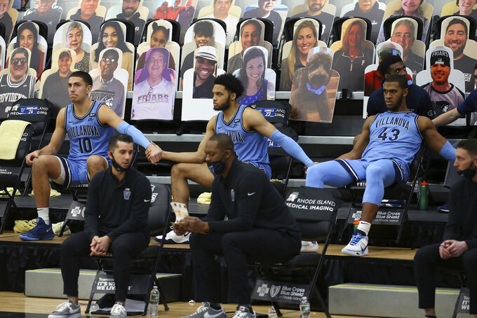 Villanova's Cole Swider (10) Caleb Daniels, center, and Eric Dixon (43) hold hands on the bench during an NCAA college basketball game against Providence in Providence, R.I., Saturday, March 6, 2021. Providence won, 54-52. (AP Photo/Stew Milne)