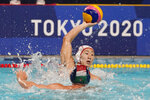 Japan's Toi Suzuki, top, protects the ball from Hungary's Daniel Angyal, bottom, during a preliminary round men's water polo match at the 2020 Summer Olympics, Tuesday, July 27, 2021, in Tokyo, Japan. (AP Photo/Mark Humphrey)