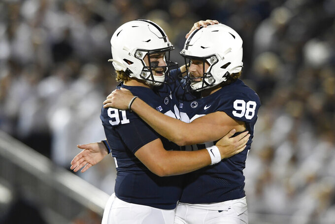 Penn State place kicker Jordan Stout (98) celebrates with Chris Stoll (91) after kicking a 50-yard field goal in the fourth quarter of their NCAA college football game in State College, Pa., on Saturday, Oct. 2, 2021. Penn State defeated Indiana 24-0. (AP Photo/Barry Reeger)