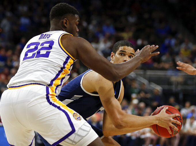 Yale 's Paul Atkinson, right, looks for a shot over LSU's Darius Days (22) during the first half of a first round men's college basketball game in the NCAA Tournament in Jacksonville, Fla., Thursday, March 21, 2019. (AP Photo/Stephen B. Morton)