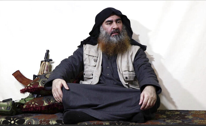 "FILE - This file image made from video posted on a militant website Monday, April 29, 2019, purports to show the leader of the Islamic State group, Abu Bakr al-Baghdadi, being interviewed by his group's Al-Furqan media outlet. No longer burdened by territory and administration, Islamic State group leader Abu Bakr al-Baghdadi outlined the new path forward for his group: Widen your reach, connect with far-flung militant groups and exhaust your enemies with a ""war of attrition."" (Al-Furqan media via AP, File)"