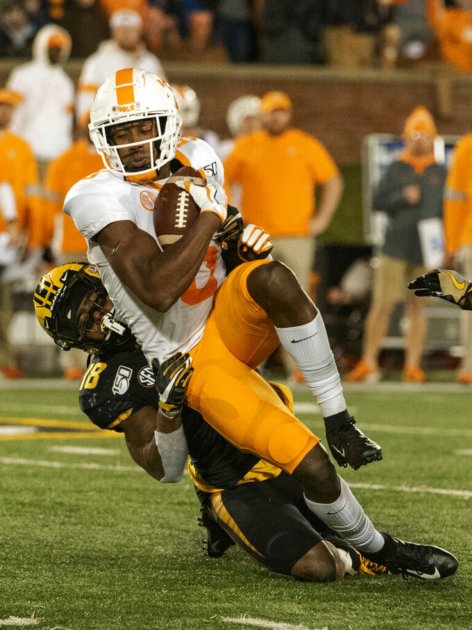Tennessee wide receiver Josh Palmer, top, is tackled by Missouri's Joshuah Bledsoe during the fourth quarter of an NCAA college football game, Saturday, Nov. 23, 2019, in Columbia, Mo. Tennessee won the game 24-20. (AP Photo/L.G. Patterson)
