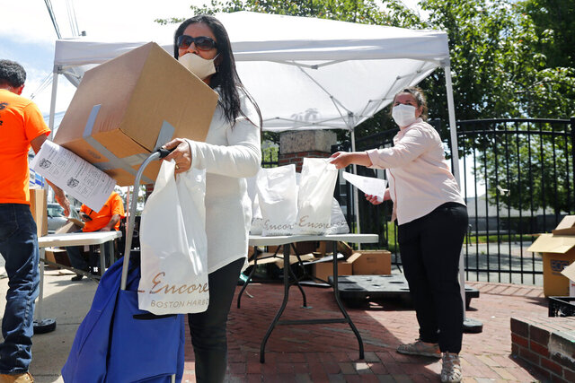 A woman receives a box of food Tuesday, June 2, 2020 at a pop-up pantry in Chelsea, Mass. (AP Photo/Elise Amendola)