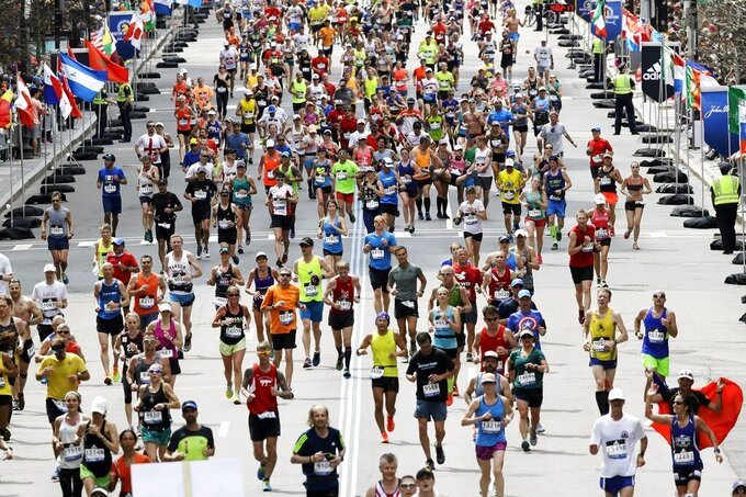 FILE - In this April 17, 2017, runners  in the 121st Boston Marathon head down the stretch to the finish line in Boston. The 124th Boston Marathon is scheduled for Monday, April 20, 2020. Boston Marathon organizers say they're postponing the prestigious race until Sept. 14 because of concerns over the coronavirus pandemic. (AP Photo/Charles Krupa, File)