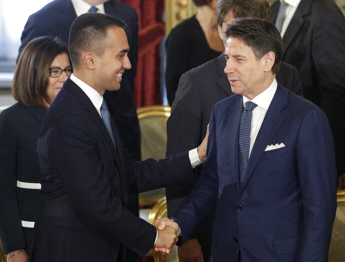 Prime Minister Giuseppe Conte, right, shakes hands with Foreign Minister Luigi Di Maio during a swearing-in ceremony at the Quirinale Presidential Palace, in Rome, Thursday, Sept. 5, 2019. Italian Premier Giuseppe Conte forged a new coalition government Wednesday that teams up the populist 5-Star Movement and center-left Democrats in an unusual alliance of rivals to banish for now the specter of early election that likely could have seen the triumph of Italy's fast-rising right-wing forces. (AP Photo/Andrew Medichini)