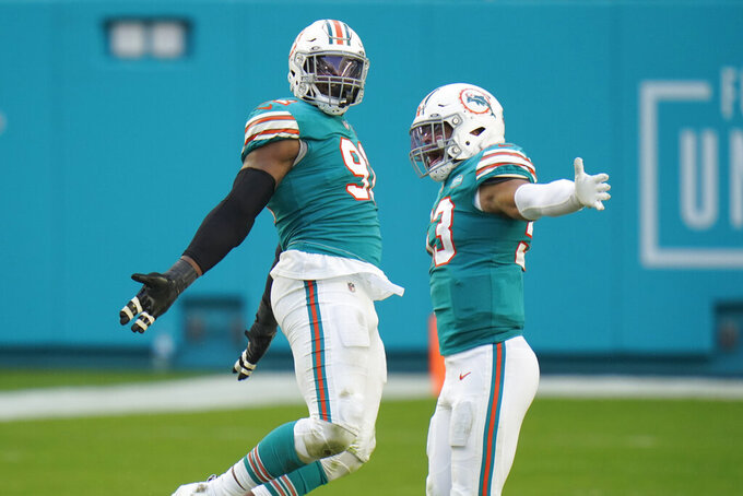 Miami Dolphins middle linebacker Kyle Van Noy (53) celebrates with defensive end Emmanuel Ogbah (91) after Ogbah sacked New England Patriots quarterback Cam Newton during the second half of an NFL football game, Sunday, Dec. 20, 2020, in Miami Gardens, Fla. The Dolphins defeated the Patriots 22-12.(AP Photo/Chris O'Meara)