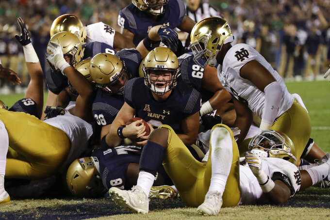 Navy quarterback Zach Abey, center, scores a touchdown during the second half of an NCAA college football game against Notre Dame, Saturday, Oct. 27, 2018, in San Diego. (AP Photo/Gregory Bull)