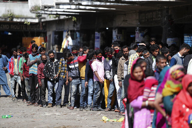 "Indian passengers who got stranded at a bus terminal line up for free food being distributed by shop keepers during a day long lockdown amid growing concerns of coronavirus in Jammu, India, Sunday, March 22, 2020. India is observing a 14-hour ""people's curfew"" called by Prime Minister Narendra Modi in order to stem the rising coronavirus caseload in the country of 1.3 billion. India's government has made fervent appeals to the public to practice social distancing, but experts say, the same is nearly impossible in many Indian cities that are among the world's most densely populated areas. For most people, the new coronavirus causes only mild or moderate symptoms. For some it can cause more severe illness. (AP Photo/Channi Anand)"