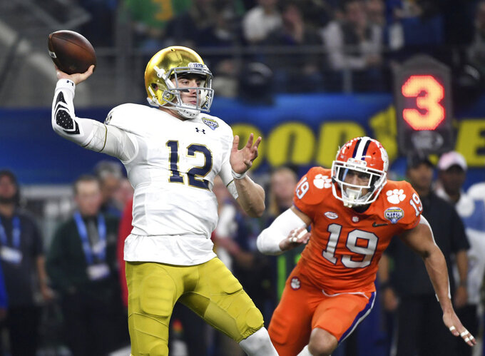 Notre Dame quarterback Ian Book (12) throws a pass under pressure from Clemson safety Tanner Muse (19) in the first half of the NCAA Cotton Bowl semi-final playoff football game, Saturday, Dec. 29, 2018, in Arlington, Texas. (AP Photo/Jeffrey McWhorter)