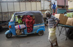 A Sri Lankan man transports a load of imported onions and garlic in an autorickshaw as an elderly laborer pulls a load of goods at a wholesale market during travel restrictions imposed to curb the spread of coronavirus in Colombo, Sri Lanka on June 16, 2021. Sri Lanka has cut back on imports of farm chemicals, cars and even its staple spice turmeric as its foreign exchange reserves dwindle, hindering its ability to repay a mountain of debt as the South Asian island nation struggles to recover from the pandemic. (AP Photo/Eranga Jayawardena)