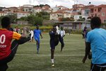 In this Saturday, May 4, 2019, Francis Kalombo from Congo, center, warms up with other players of Cosmos FC ahead of a friendly match between African team and Afghan migrants at a soccer field, in Moria village, on the northeastern Aegean island of Lesbos, Greece. A 10-minute walk from Europe's largest refugee camp is a place where residents of the Moria camp on the Greek island of Lesbos can briefly forget about their tiny container-homes and crowded tents and instead worry about corner kicks and throw-ins. Many of the players hope to turn professional and leave the camp, where they are forced to remain indefinitely under European Union rules designed to limit the number of migrants and refugees reaching the mainland. (AP Photo/Thanassis Stavrakis)