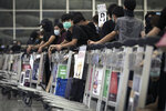 Protesters use luggage trolleys to block the departure gates during a demonstration at the Airport in Hong Kong, Tuesday, Aug. 13, 2019. Protesters severely crippled operations at Hong Kong's international airport for a second day Tuesday, forcing authorities to cancel all remaining flights out of the city after demonstrators took over the terminals as part of their push for democratic reforms. (AP Photo/Vincent Thian)